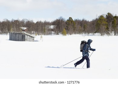 A skier with a large backpack on a wintery snow filled landscape.