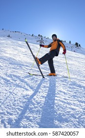 skier lifting his leg with the ski on in the snow