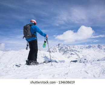 Skier looking out over mountain landscape.
