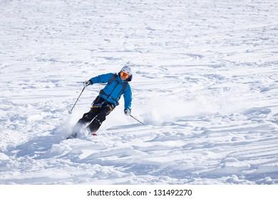 Skier making big carving turn in powder snow.