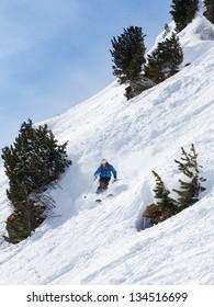 Skier making turn between trees in powder snow.
