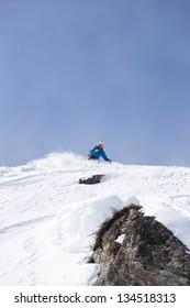 Skier making turn in powder snow above rock.