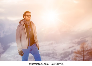skier man detail wearing anorak jacket with sunglasses portrait. exploring snowy land walking and skiing with alpine ski. Europe Alps. Winter sunny day, snow, wide shot, warm sun flare.travelling