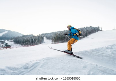 Skier man at jump from the slope of mountains in blue jacket with forest in background. Side view