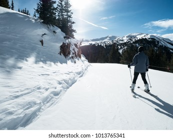 SKIER WITH NICE VIEW OF SKI TRIAL AND PINE TREES IN COLORADO IN BRIGHT BLUE SKY