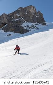 Skier on hard packed snow below chute.