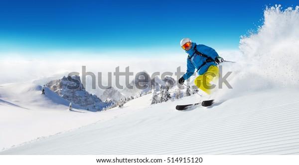Skifahrer auf der Piste, die hinunter in die wunderschöne Alpenlandschaft führt. Blauer Himmel auf Hintergrund. Freier Textraum