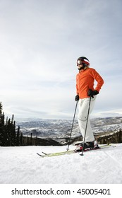 Skier on ski slope with mountains in background. Vertical shot.