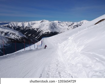 Skier on the slope and peaks of the mountains in the background