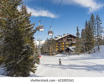 Skier on a snowy ski slope piste in winter alpine mountain resort with coniferous pine trees and hotel