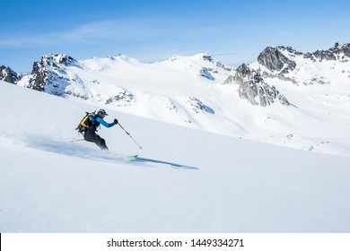 Skier on sunny day and fresh snow ripping down the slope above the Snowbird Glacier in Hatcher Pass, Alaska.