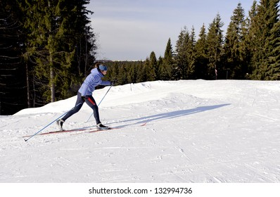 Skier on a walk in the park in winter
