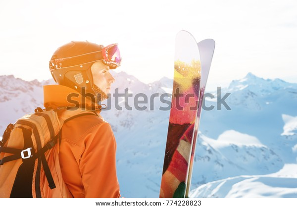 A skier in an orange overall with a backpack on his back wearing a helmet and with ski poles in his hands is standing on a precipice in front of a snowy abyss in the background of a beautiful