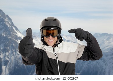 Skier pointing on his helmet in front of mountains