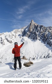 Skier pointing towards mountain peak (Aiguille du Dru) in Chamonix, France.