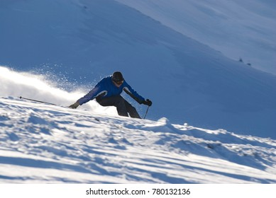 The skier quickly descends from the mountain
