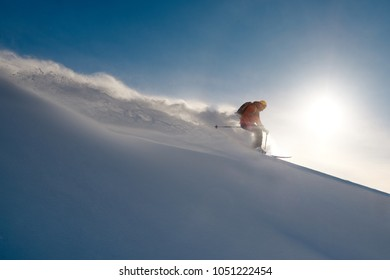 skier rides freeride on powder of snow leaving wave on sky background