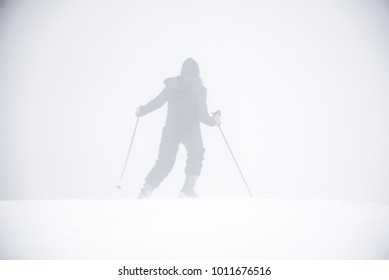 Skier silhouette in dense fog on a snowy mountain top