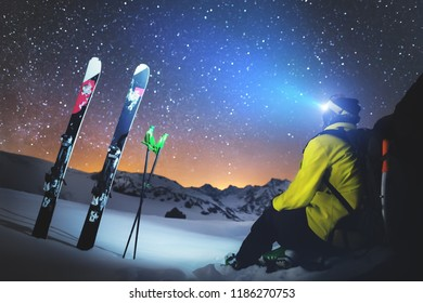 A skier sits at a stone in the mountains at night against a starry sky next to skis and sticks. The concept of extreme in the mountains at night