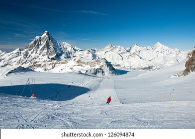 Skier and ski lifts in front of the Matterhorn