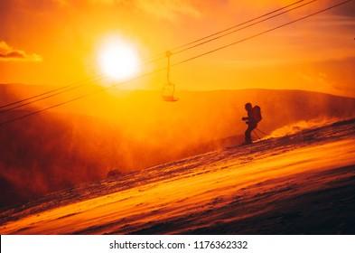 Skier in ski resort - orange sport photo, colorful winter sunset light