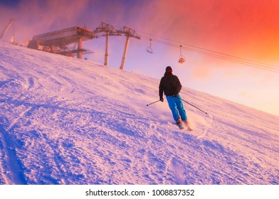 Skier in ski resort. Red sunset sky in background.