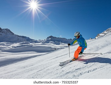 Skier skiing downhill during sunny day in high mountains