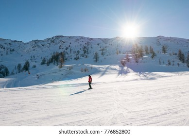 Skier skiing downhill during sunny day in high mountains Alps in Sauze D'Oulx piedmont Italy