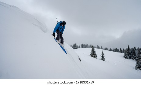 Skier skiing downhill in high mountains during windy cold weather. Snow falling from heavy grey clouds. Winter web banner design.