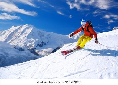 Skier skiing downhill in high mountains, Matterhorn area, Switzerland