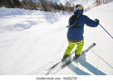 skier skiing downhill on fresh powder snow  with sun and mountains in background