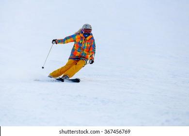 Skier skiing in fresh snow on ski slope