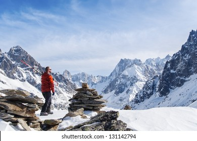 Skier with skis on shoulder looking out over mountain landscape in Chamonix, France.