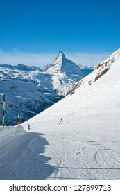 Skier and snowboarder on the slope with Matterhorn in background
