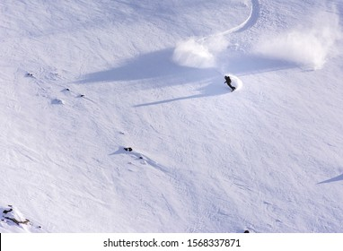 skier snowboarder riding through field of powder