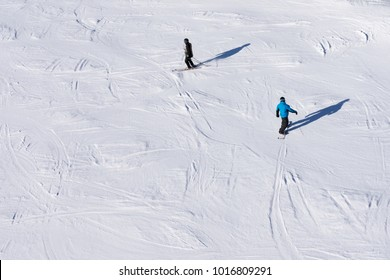 Skier and snowboarder skiing and snowboarding on a slope, top view.