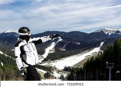 skier is standing on top of the mountain and points with his hand forward