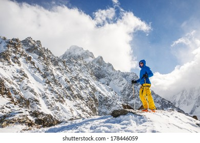 Skier standing on top of pass with mountains in the background