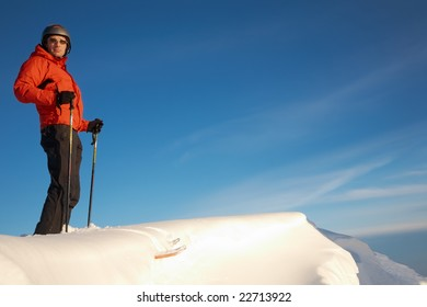 Skier standing at the top of a snowy ridge over a clear blue sky, italian alps; horizontal frame