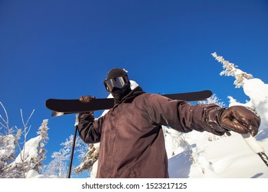 Skier in suit mask stands in hands with skis on background blue sky and forest, lowest point of shooting.
