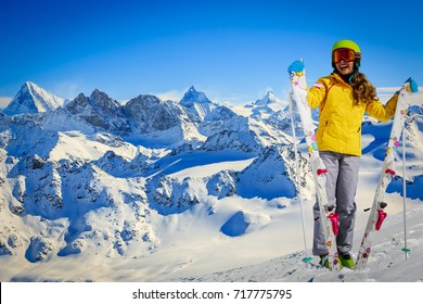Skier teenager along a snowy ridge with skis. In background blue sky and shiny sun and Swiss Alps.  Adventure winter sport.