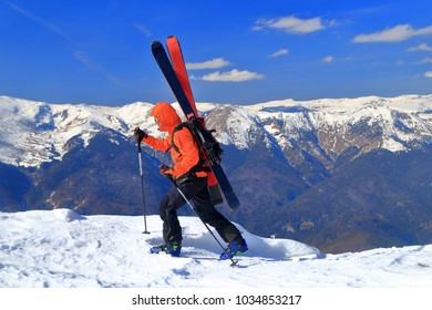 Skier traversing a snow covered ridge with skis attached to the backpack