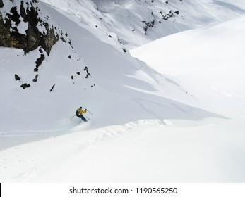 A skier turning down a slope of fresh powder while ski touring in the Alps
