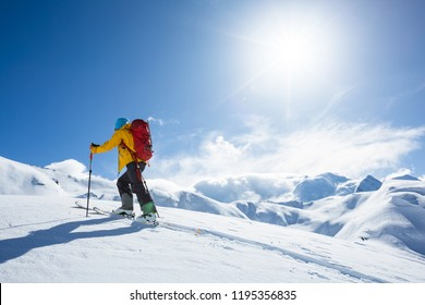 A skier is walking up the hill. Skitouring in Alps. Sunny weather.
