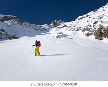 Skier walking up slope in powder snow