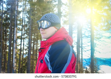Skier in winter forest, mountains scene with sunlight, portrait of young man in sunglass mask, ski resort concept