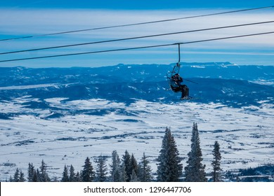Skiers ascend the chairlift to the top of the ski slopes of Steamboat Springs, in the Rocky Mountains of Colorado, lined by Pine and Aspen trees.
