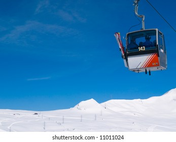Skiers being transported up ski slopes in Gondola Cablecar