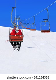 Skiers couple in red Santa hats go on a ski lift against winter snowy mountain landscape and blue sky - Christmas greeting card or vacation concept