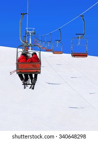 Skiers couple in red skisuits go on a ski lift against winter snowy mountain landscape and blue sky
